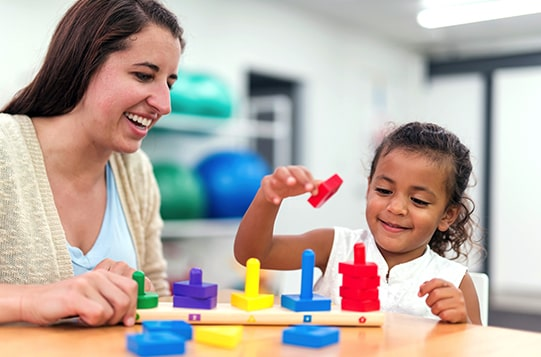 woman and child with color sorting toy