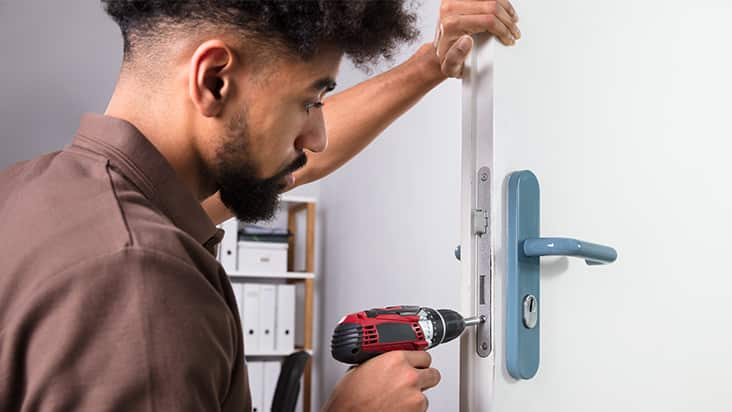 man working on a door lock