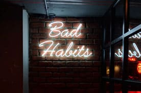 "A Neon sign that displays the words ""bad habits"""