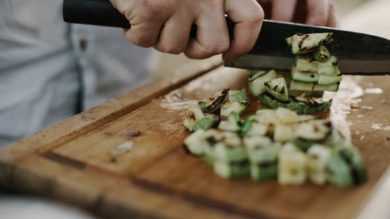 person chopping vegetables on a wooden cutting board