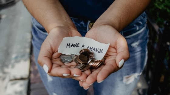 person holding coins with paper that says make a change