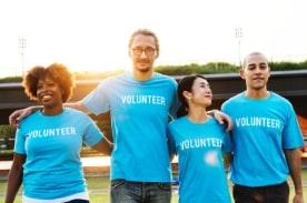 "four people wearing blue shirts with text ""volunteer"""