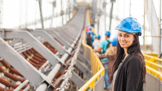 Woman wearing a hard hat overseeing manufacturing & construction