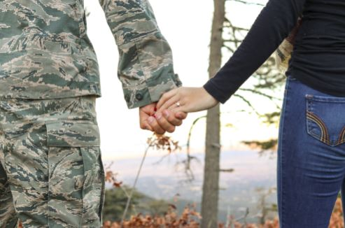 Service member and partner holding hands