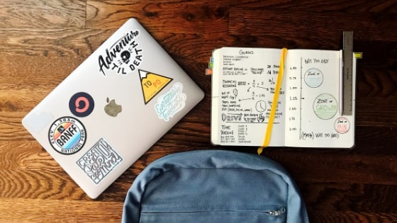 backpack, laptop, and notebook on table.