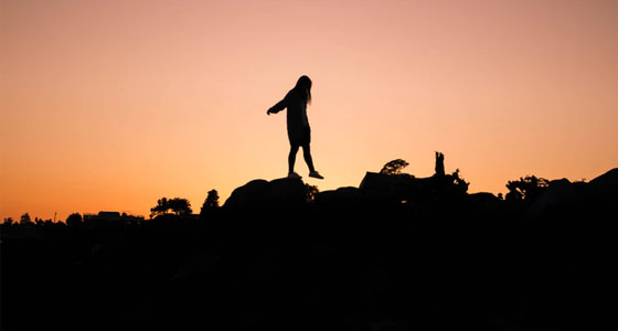 girl standing on mountains with hands in the air