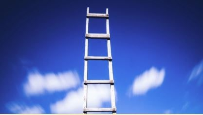 simple wooden ladder against blue sky with clouds